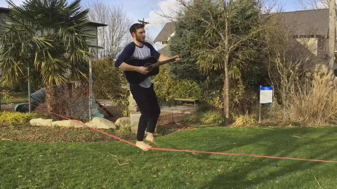Guy Attempts to Play Guitar While Slacklining