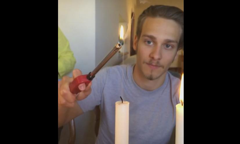 Guy Lights a Candle Through its Wisp of Smoke