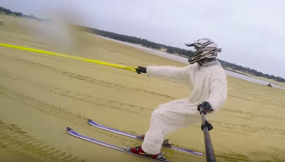 Skiing on Sand as a Yeti Tracked by a Quad Bike